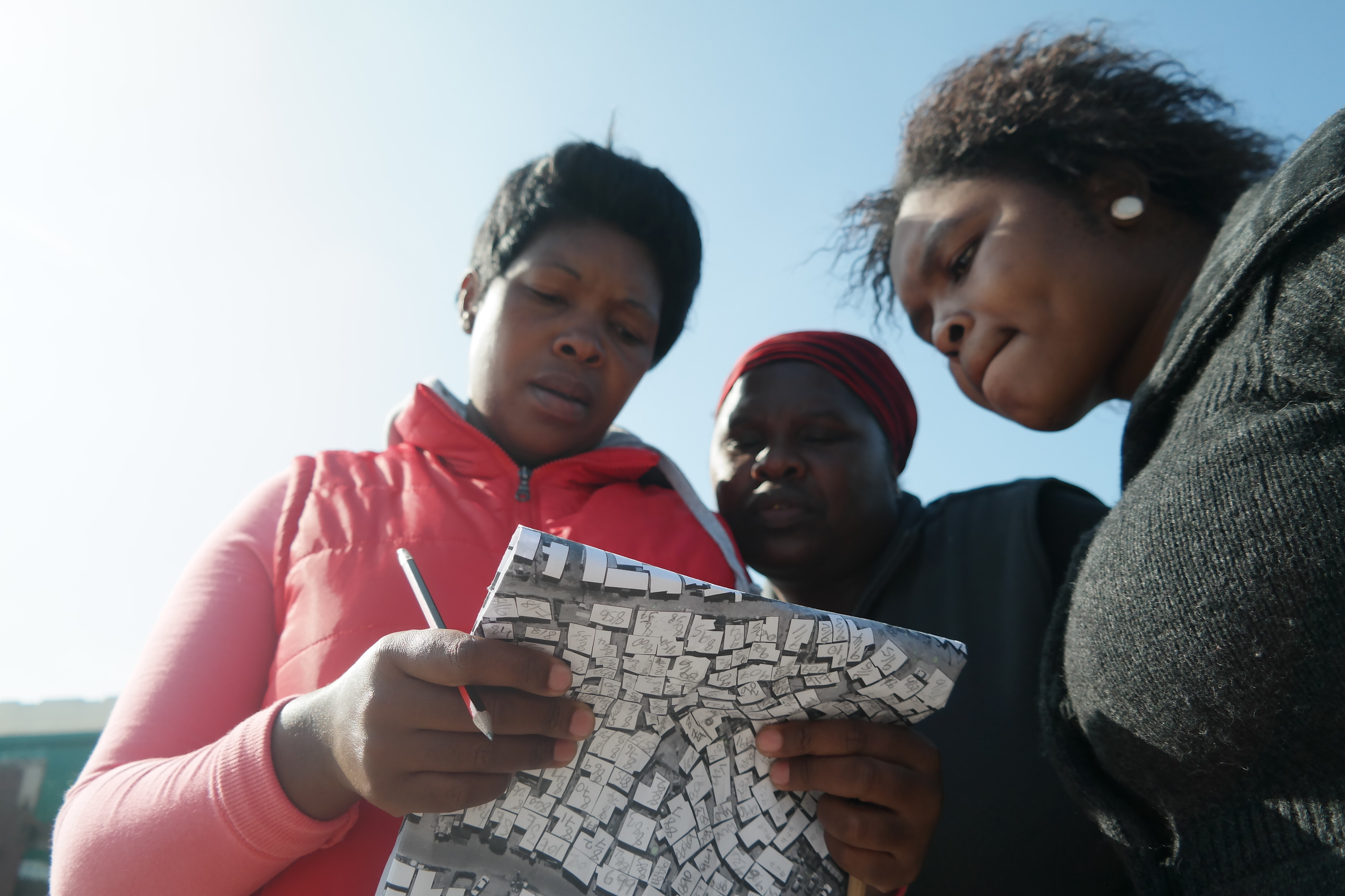 Before setting out to number shacks, the numbering team reviews the settlement layout map.