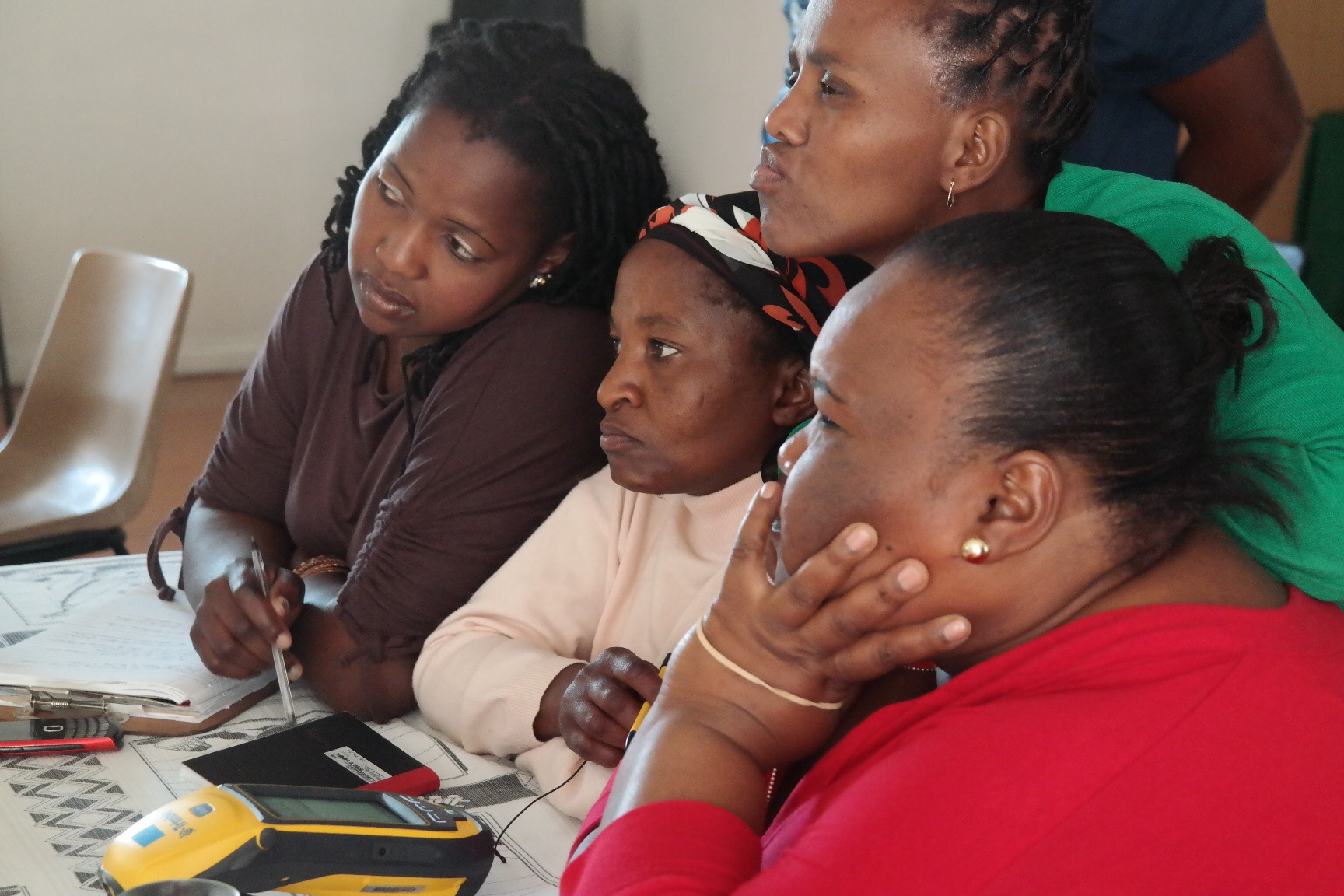 Community enumerators learn the basics of conducting a household-level survey using a data collection device called the Trimble during an enumerations training workshop.