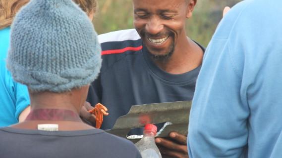 A community member in Innesfree, Johannesburg assembles a 'Litre of Light' bottle