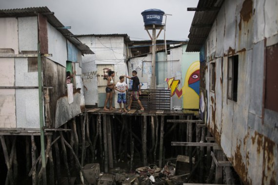 """In this Jan. 29, 2016 photo, Tainara Lourenco, who's five months pregnant, stands outside her stilt home that stands over polluted water in a slum in Recife, Brazil. Lourenco became pregnant at a scary moment — the dawn of an extraordinary Zika outbreak, as authorities came to suspect that the virus was causing an alarming spike in a rare birth defect called microcephaly. """"If you have to get sick you will get sick,"""" she said. """"It's everywhere."""" (AP Photo/Felipe Dana)"""