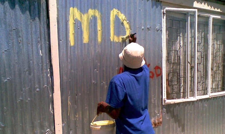 Community members number shacks, one phrase of the enumeration process