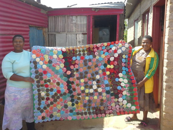 Manana (left) and Nthabiseng (right) display their bedding (income generation) project for Tshwarellang saving scheme in Free State during the exchange.